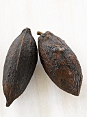 Two cacao fruits on white wooden surface