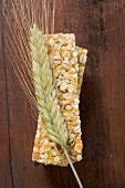 Muesli bars with ear of barley on wooden background