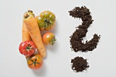 Two carrots, four tomatoes & soil forming a question mark