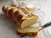 Bread plait with pearl sugar, milk jug & eggs in background