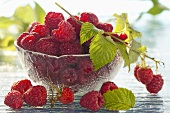 Fresh raspberries with leaves in a bowl