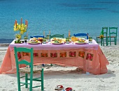 A table on the beach laid with fruit and drinks