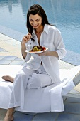 Woman dressed in white eating salad at swimming pool