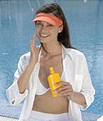 Weiss gekleidete Frau cremt sich am Swimmingpool ein