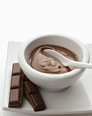 Chocolate mask in small bowl and pieces of chocolate