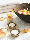 Rose petals in a wooden bowl and tealights