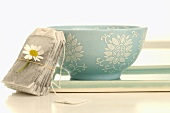 Tea bag with chamomile flower and drinking bowl