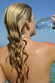 Woman drinking water out of a bottle by the sea