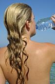 Frau trinkt Wasser aus einer Flasche am Meer