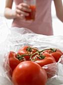 Tomaten, im Hintergrund Frau mit einem Glas Tomatensaft