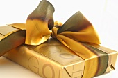 Gift wrapped in gold paper with bow