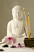Buddha with cyclamen flowers, candles, joss sticks & hematite