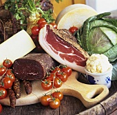 Assorted sausage products, tomatoes, cheese, horseradish, cabbage
