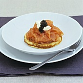 Smoked salmon with sour cream and caviar on blini