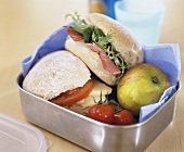 Two sandwiches, apple and tomatoes in a lunch box