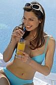 Frau auf Liege am Swimming Pool mit Sonnenbrille und Getränk