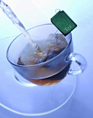 Pouring boiling water onto tea bag