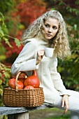 Young woman with basket and cup in park in autumn