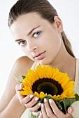 Junge Frau hält eine Sonnenblume in der Hand