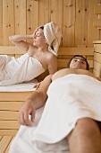 Frau und Mann liegen in der Sauna
