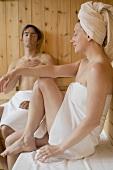 Frau und Mann sitzen in der Sauna