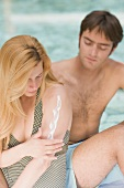 Frau und Mann sitzen am Pool, Frau cremt sich ein