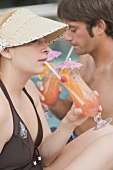 Man and woman drinking Planter's Punch by pool