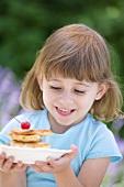 Little girl holding plate of apple pancakes