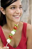 Junge Frau mit Tomaten-Mozzarella-Spiesschen