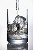 Wasser ins Glas mit Eiswürfeln eingiessen