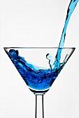 Blue Curacao in ein Glas gießen