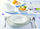 Place-setting with white plate, glass of water and salad