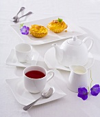 A cup of fruit tea, tea things and small cakes