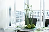Gedeckter Esstisch mit Blumengesteck vor hellem Balkon