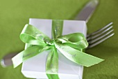 Small gift with green ribbon on knife and fork