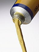 Mustard being squeezed out of a tube