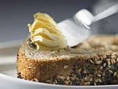 Butter knife with butter on seed bread