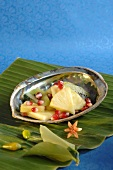 Pineapple, kiwi fruit & pomegranate seeds in abalone shell