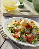 Cucumber salad with melon balls and strawberries