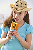 Girl in hat eating fish and salad sandwich at picnic
