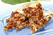 Pieces of tarte flambée with onion and bacon topping