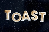 Toast letters spelling the word TOAST on black background