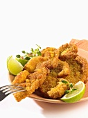 Breaded escalopes with lime wedges