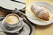 Caffe crema, a croissant and a sugar tin