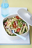 Pasta salad with ham, rocket and tomatoes in a plastic box