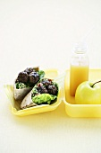 Pita bread with meat balls and tabbouleh, an apple and a smoothie in a lunchbox