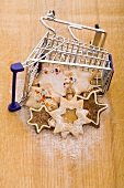 Various Christmas biscuits in a mini shopping trolley