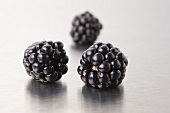Three blackberries on a metal surface (close-up)