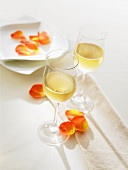 Two glasses of white wine on a table decorated with flower petals
