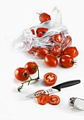 Tomatoes in a plastic bag with a knife and a salt shaker